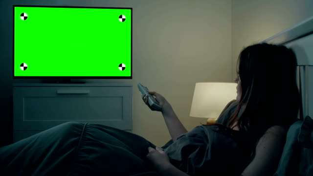 vídeos de stock e filmes b-roll de watching tv woman in bed changing channel, chroma key screen. - controlo remoto