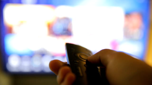 Watching TV-changing channels, blurred TV