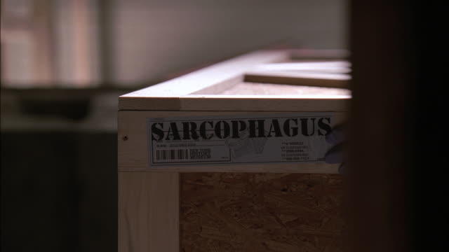 pov watching workers opening crate in museum warehouse labeled sarcophagus from behind wooden slats / los angeles, california, united states - hiding stock videos and b-roll footage