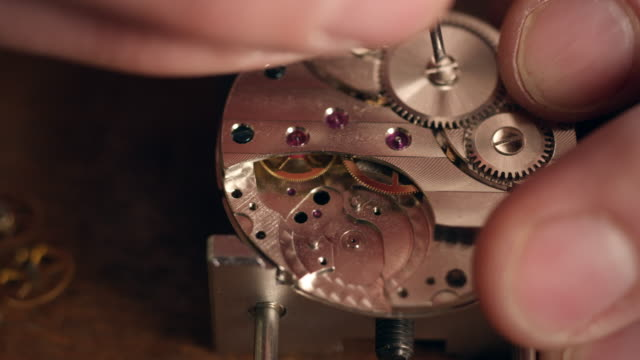 watchmaker assembling watch (shot on red epic) - clockworks stock videos & royalty-free footage
