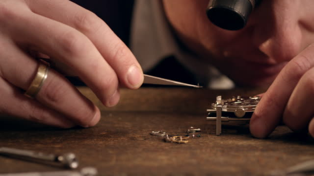 Watchmaker assembling watch