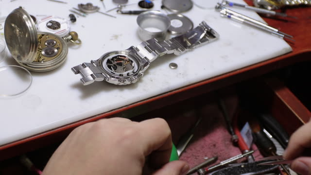 watchmaker changing battery on wristwatch at his workshop - wrist watch stock videos & royalty-free footage
