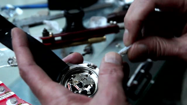 hd: watchmaker is changing battery - changing clock stock videos and b-roll footage