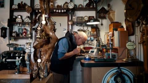vídeos y material grabado en eventos de stock de relojero reparando reloj antiguo - anticuario anticuado