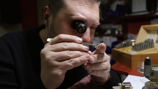 レトロな懐中時計を修理する目のルーペを持つ時計メーカー - 骨董品点の映像素材/bロール