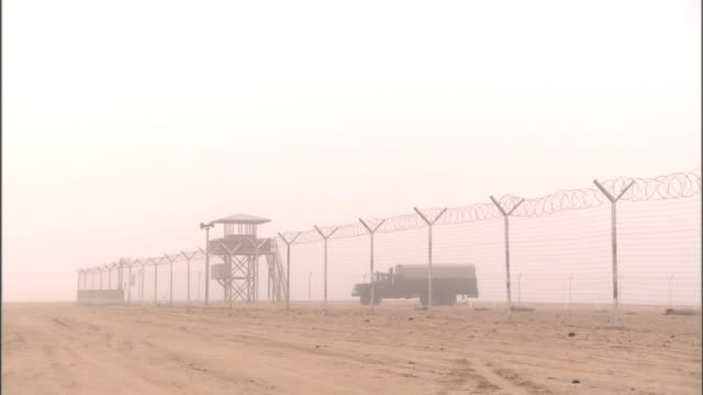 watchtower military transport truck behind fence of unidentifiable military base hazy sky above no visible people sandstorm camp middle east - military base stock videos & royalty-free footage