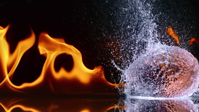 slo mo ld water balloon exploding and extinguishing the fire flames - super slow motion stock videos & royalty-free footage