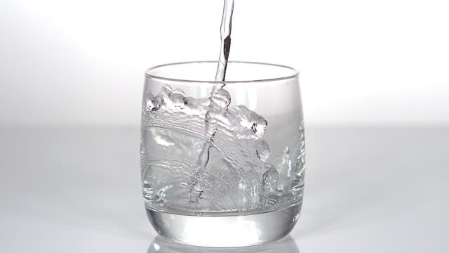 Water being poured into Glass against White Background, Slow motion