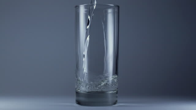 slo mo ms water being poured into glass - bicchiere video stock e b–roll
