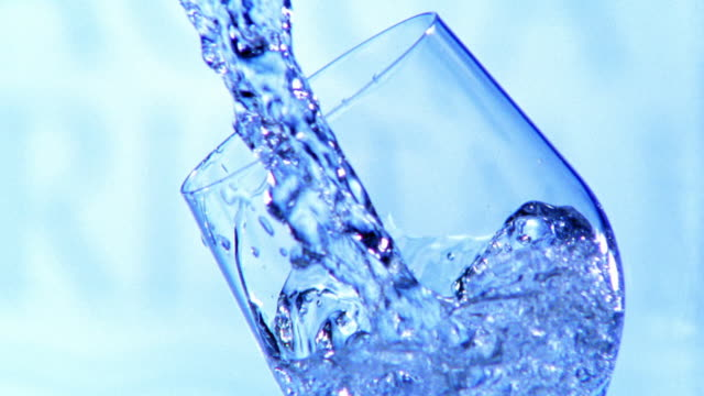 blue high speed water being poured into tilted glass + spilling out with light blue studio background - blue glass stock videos and b-roll footage