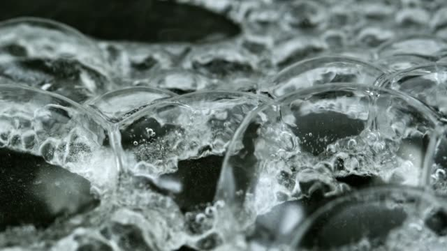 vídeos de stock e filmes b-roll de water boiling and bubbling on hot surface - close up - ferver