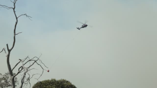 vídeos de stock e filmes b-roll de a water bombing black hawk helicopter flies towards the great lake to refill on january 22 2019 in miena australia around 40 residents from the small... - acidentes e desastres