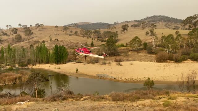 a water bombing helicopter picks up water from the murrumbidgee river near mount tennant as the fire front of the orroral valley fire creeps forward... - canberra stock videos & royalty-free footage