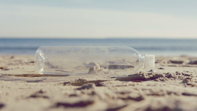 vidéos et rushes de bouteille d'eau sur la plage de grosses vagues en toile de fond - bouteille
