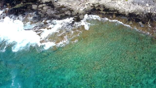vídeos de stock, filmes e b-roll de água, quebrando-se sobre um afloramento rochoso na ilha de maui - baixo posição