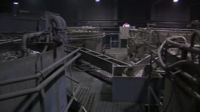 Water bubbles and foams in vats as part of the mining process.