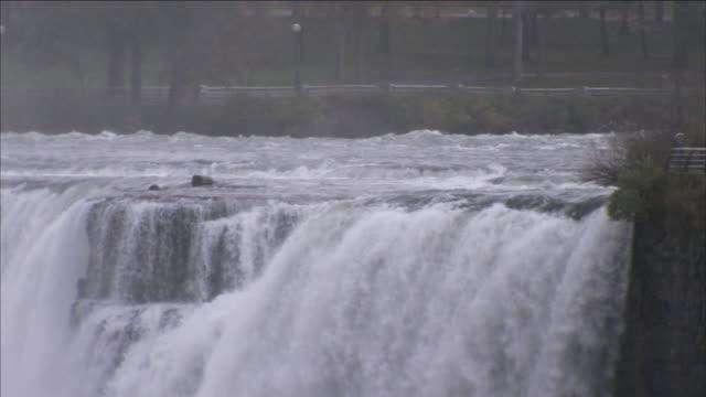 water cascades over niagara falls. - river niagara stock videos & royalty-free footage