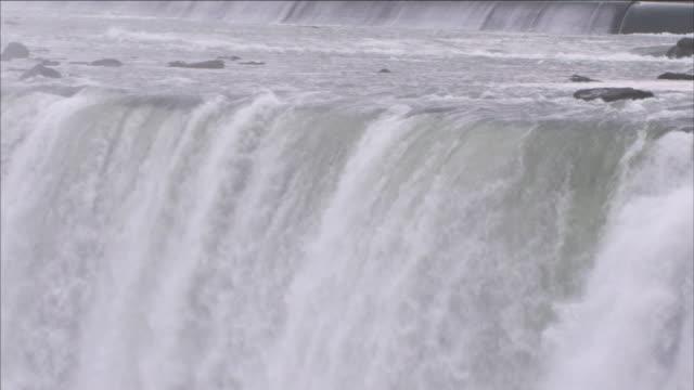 water cascades over niagara falls. - niagara falls stock videos & royalty-free footage