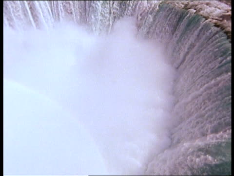 water cascades over the lip of niagara falls. - niagara falls stock videos and b-roll footage