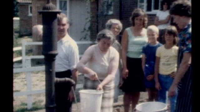 water companies announce hosepipe bans across south east; t29120612 1976 location unknown: ext woman filling bucket with water whilst man pumping... - extreme weather stock videos & royalty-free footage