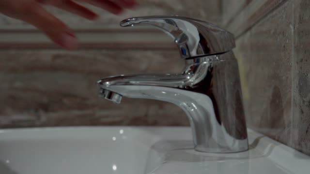 water conservation issues. environmental conservation goals. washing hands in the bathroom, close up, clean and shiny bathroom sink. - water conservation stock videos & royalty-free footage