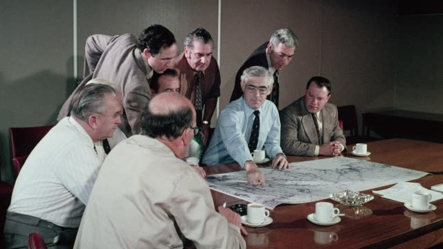 MONTAGE Water conservation members looking at and pointing to topographical map on conference table / Wales, United Kingdom