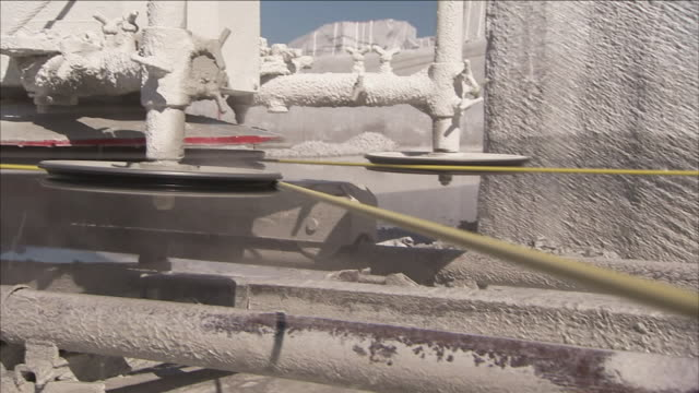 water cools the cable on a granite cutter. - granite rock stock videos & royalty-free footage