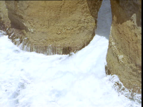 Water crashes against base of rock arch at Twelve Apostles stacks, Victoria, Australia
