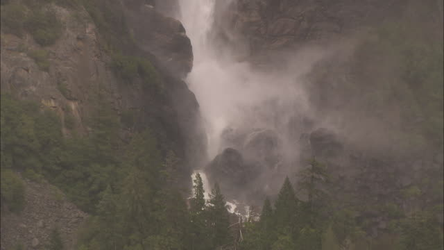 stockvideo's en b-roll-footage met water crashes down onto rocks at the base of a waterfall in the yosemite national park. - rotsmuur