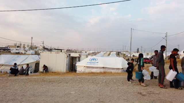water distribution truck makes its rounds at badarash idps camp which has continued to swell for syrian kurdish refugees fleeing the recent turkish... - クルド人点の映像素材/bロール