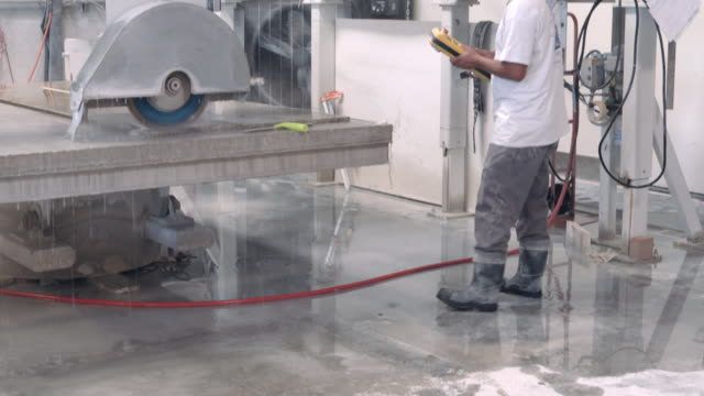 WS TU water dripping from table of computer controlled gantry saw as operator holds control in his hand and watches marble cutting process  / Thousand Palms, California, USA