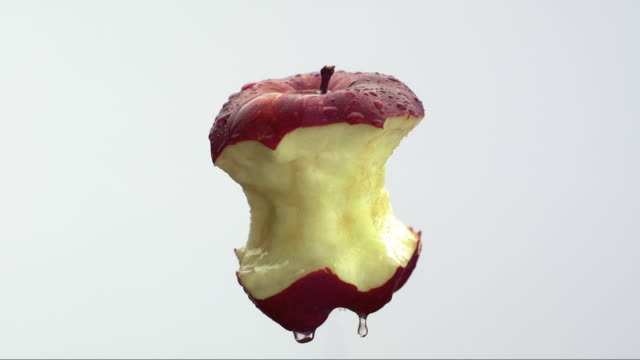 CU SLOW MO water drips off of half eaten red apple on white background