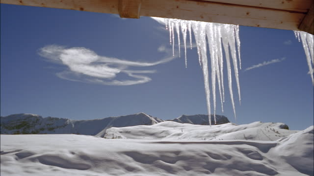 water drips off of icicles hanging on a roof. - icicle stock videos and b-roll footage