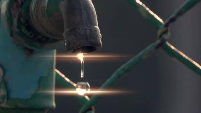 vidéos et rushes de goutte d'eau du vieux robinet avec la boucle de mouvement lent de sunray - eau robinet