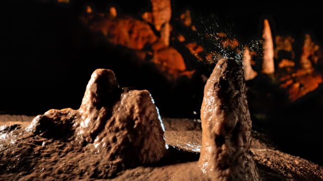 slo mo ld water droplet falling onto a stalagmite - stalagmite stock videos and b-roll footage