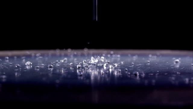 water droplets bouncing on shinny surface. - はずむ点の映像素材/bロール