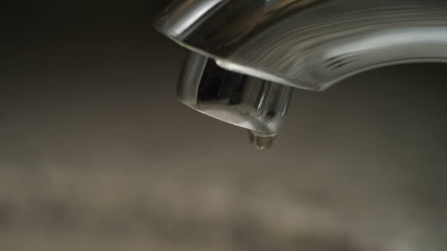 water droplets dropping dripping from silver metal faucet in unidentifiable area restroom wash room bathroom sink kitchen leak - zapfen stock-videos und b-roll-filmmaterial