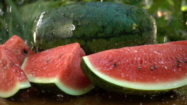 Water drops around watermelon on green background