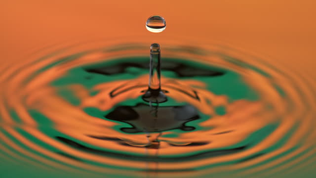 slo mo ld water drops disturbing the calm orange and green lit water surface - sine wave stock videos & royalty-free footage