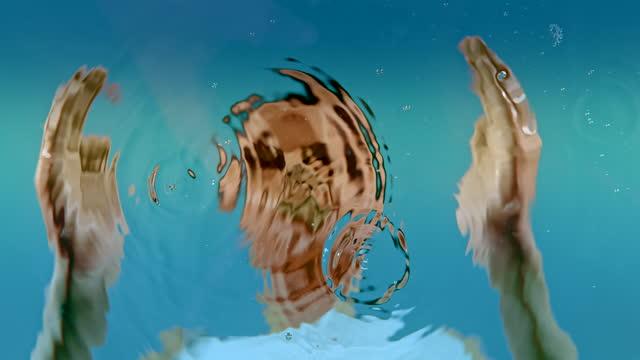 super slo mo gocce d'acqua che cadono dalle mani di una donna - acqua potabile video stock e b–roll
