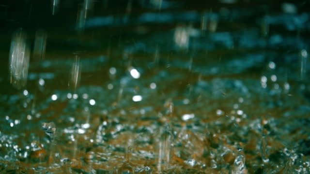 slo mo of water drops falling onto the water surface - torrential rain stock videos & royalty-free footage