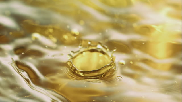 vídeos de stock e filmes b-roll de water drops making ripples and waves on golden hued water surface, in close up and slow motion - fluir