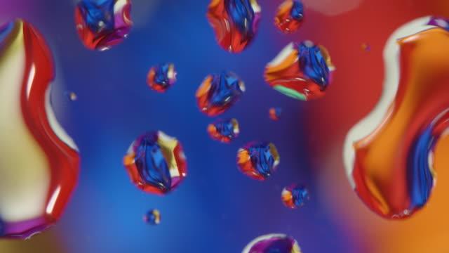 vídeos de stock, filmes e b-roll de molhe gotas no vidro colorido do fundo abstrato de vidro que gira - water form