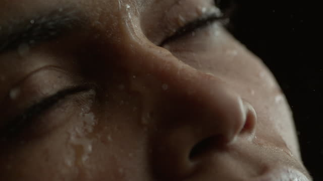 Water drops on woman's face - Close up on eyes - Face turning