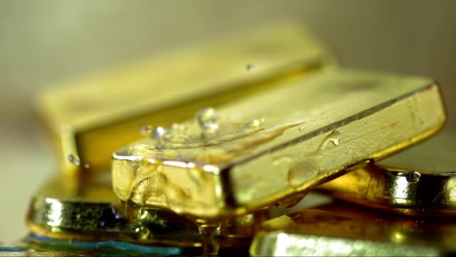 wassertropfen planschen an gold (super zeitlupe) - barren geld und finanzen stock-videos und b-roll-filmmaterial