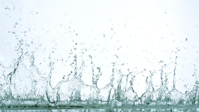 water exploding and splashing against white background, slow motion - spritzer stock-videos und b-roll-filmmaterial