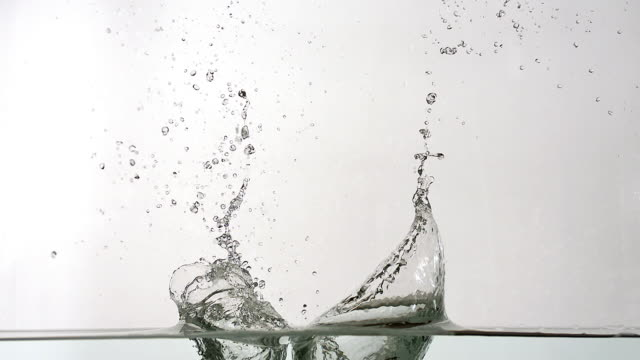 vidéos et rushes de water exploding and splashing against white background, slow motion - asperger