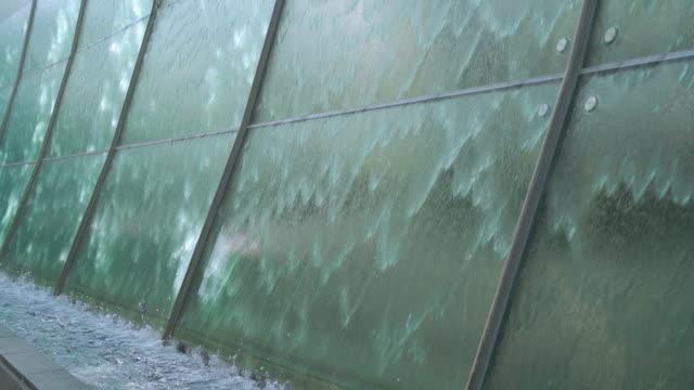 透明な緑の自然で眼鏡の壁から落ちる水 - 石材点の映像素材/bロール