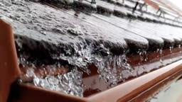 Water falling down to gutter from roof.