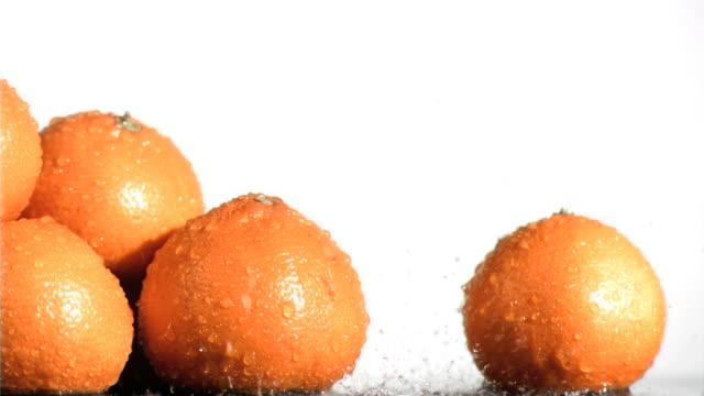 vídeos de stock, filmes e b-roll de water falling in super slow motion on oranges - grupo médio de objetos